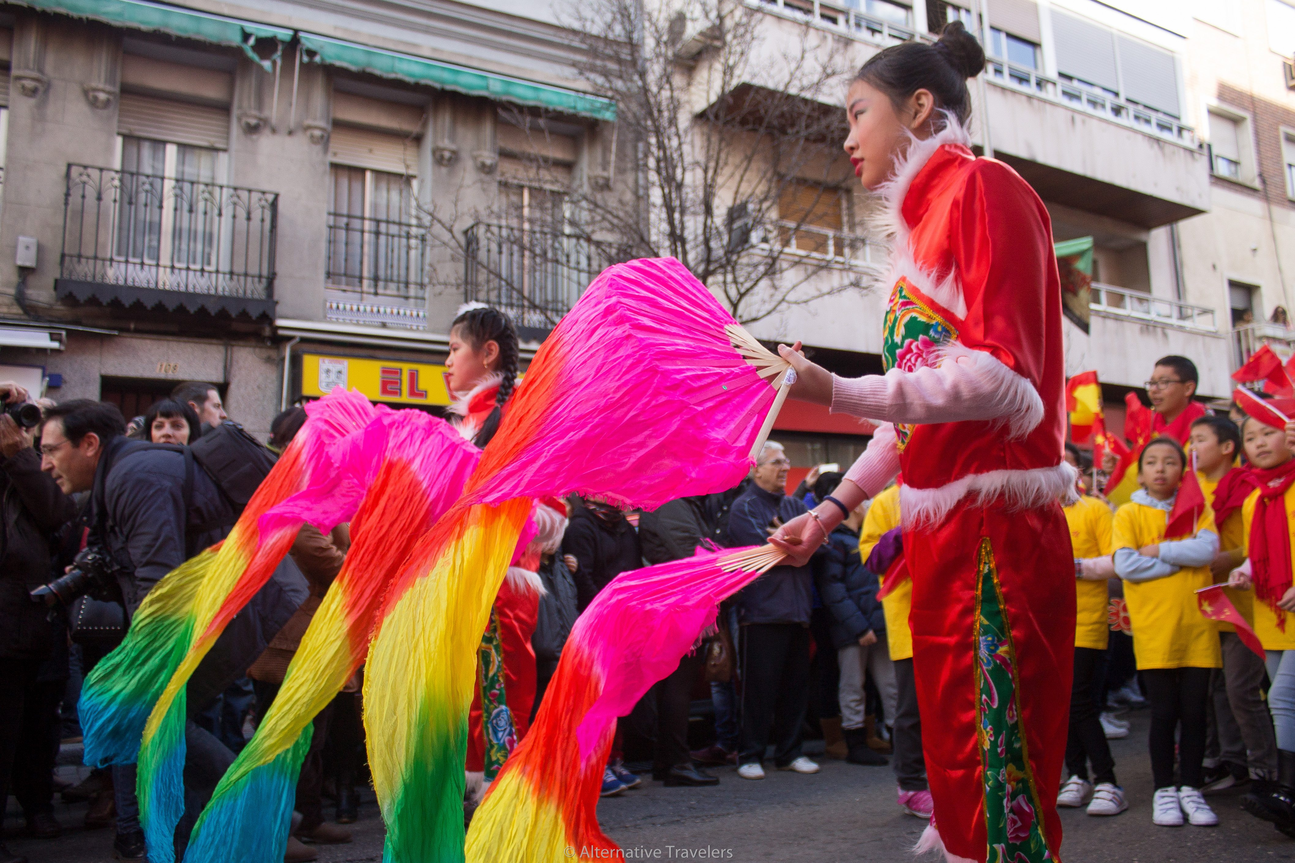 Girl waving colorful rainbow flags at Chinese New Year in Madrid