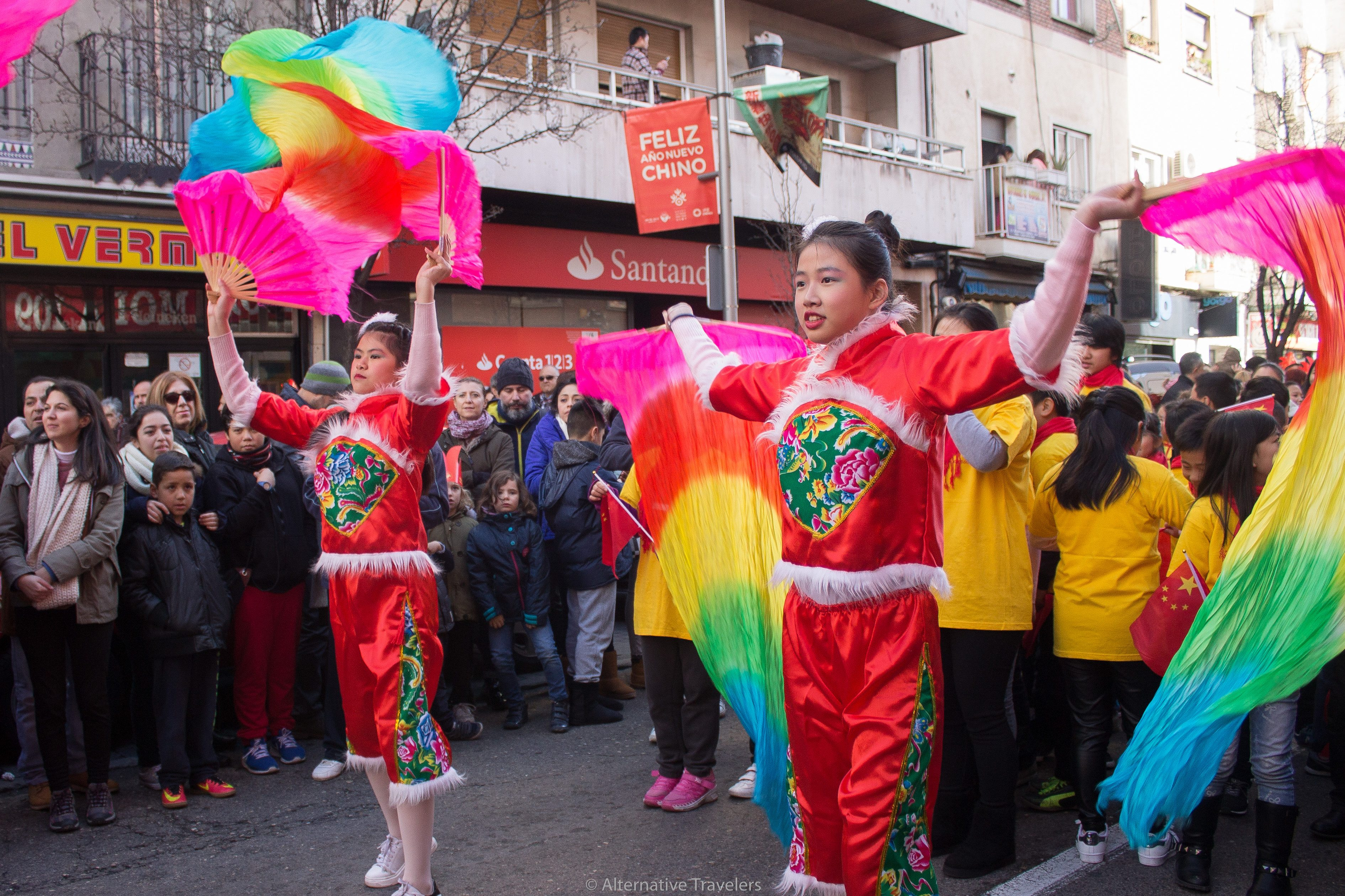 Girls waving colorful rainbow flags at Chinese New Year in Madrid
