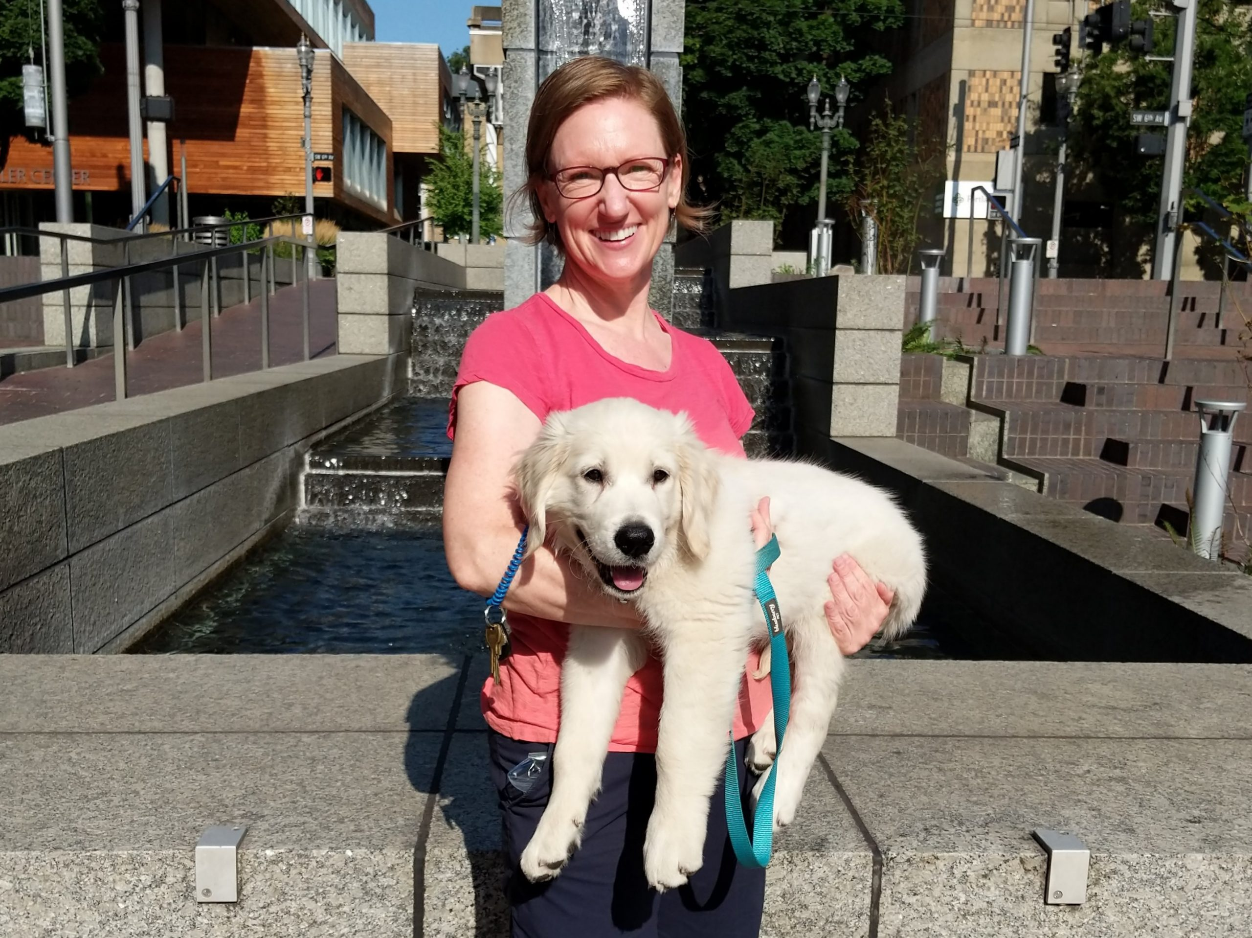 woman holding a golden retriever puppy