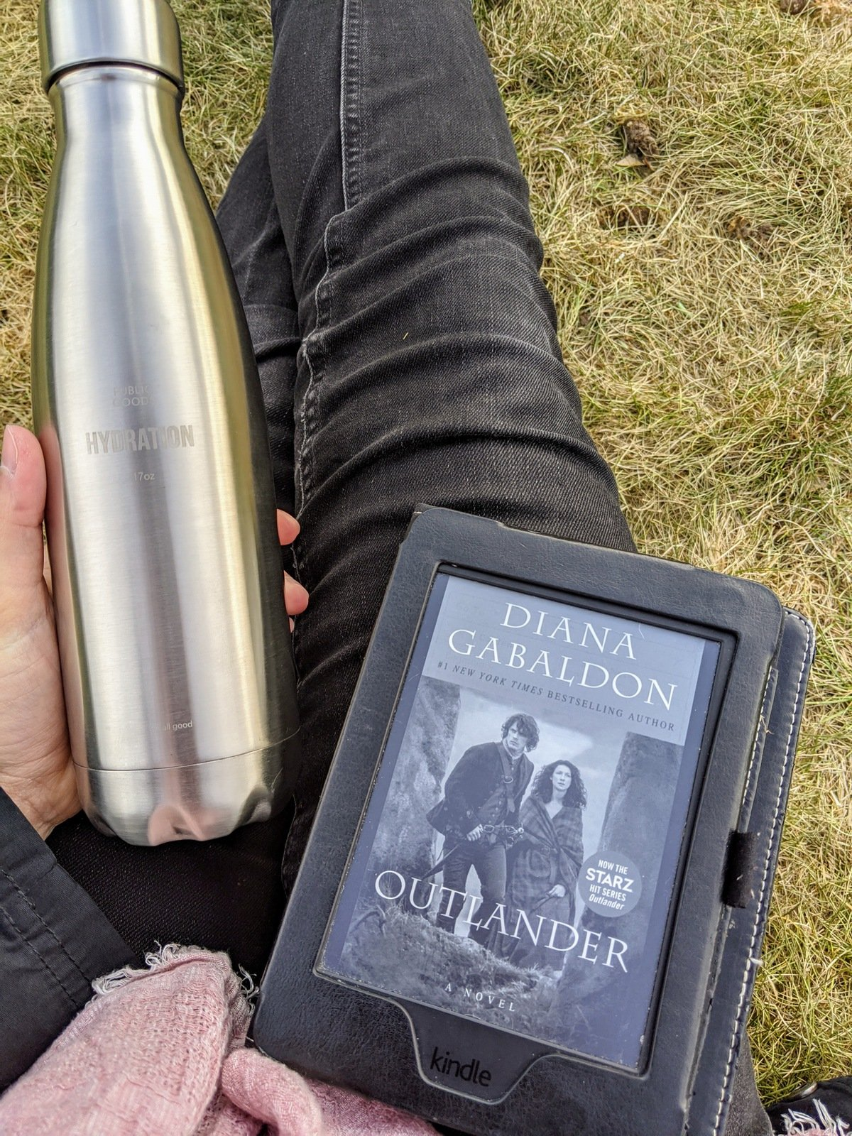 "Water bottle and Kindle with cover of ""outlander"""
