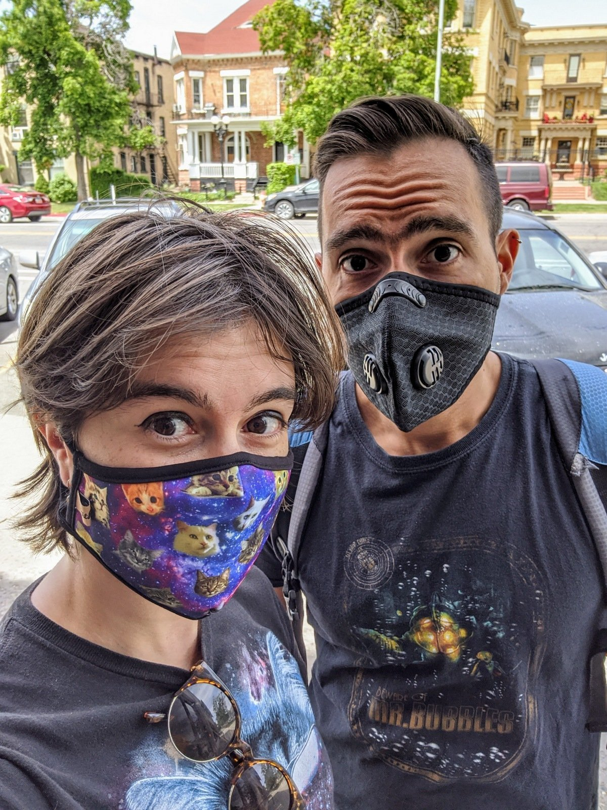 man and woman with masks on. she has a cat mask, he has a black N95 mask.