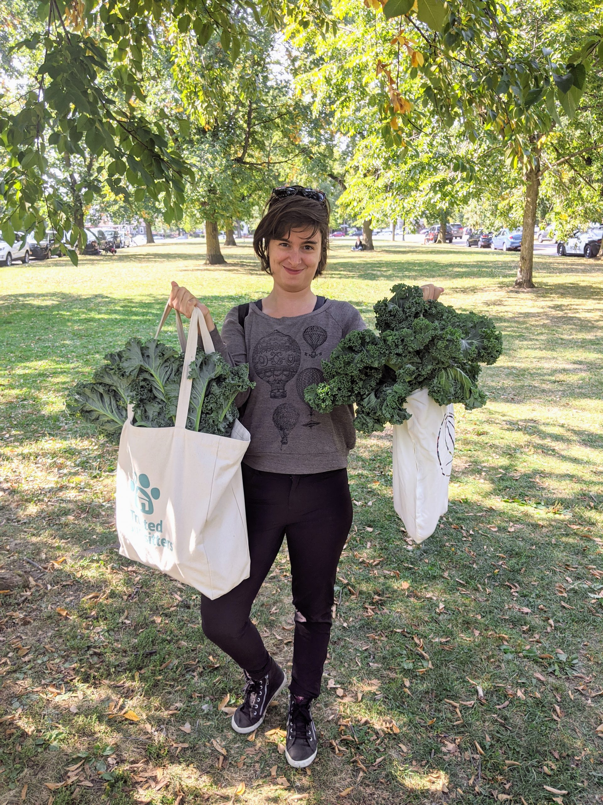 Sam with tote bags full of kale