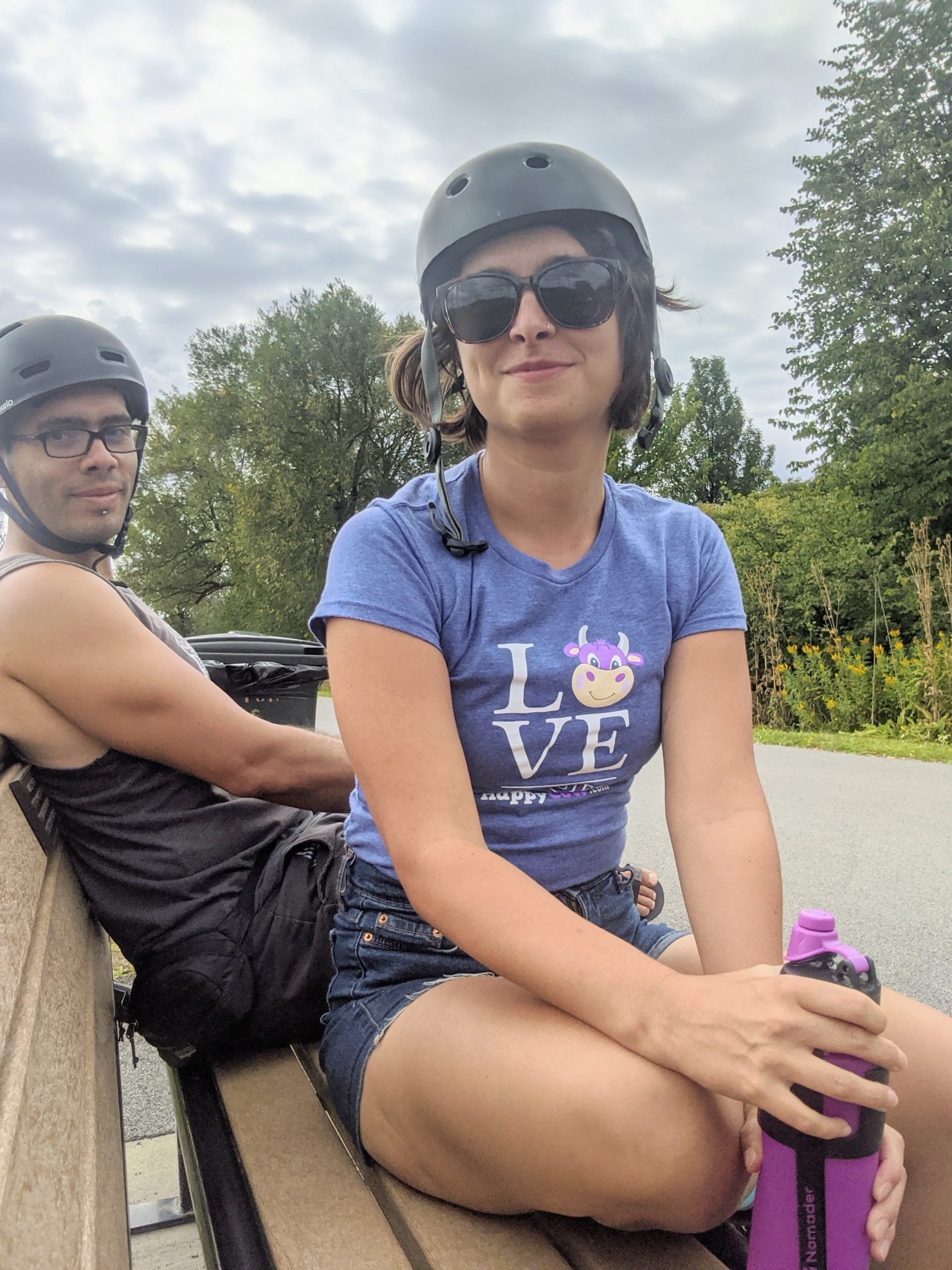 Sam and Veren sitting on a bench with bike helmets on and a purple water bottle in Sam's hands